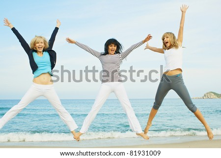 Three young girls jumping on the sea coast - stock photo