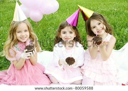 Three young girls outdoors merry, celebrate a birthday, give gifts - stock photo