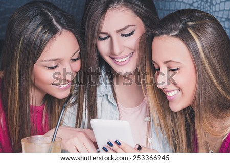 Three young girls smiling and looking at the mobile phone in a cafe - stock photo