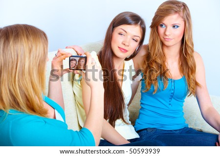Three young girls taking photos on the meeting in home. - stock photo