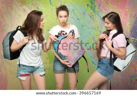 Three young girls with backpacks in the studio - stock photo