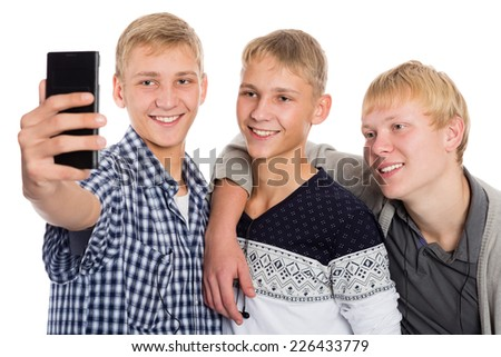 Three young guys take on self smartphone. Two of the boys twin brothers. - stock photo