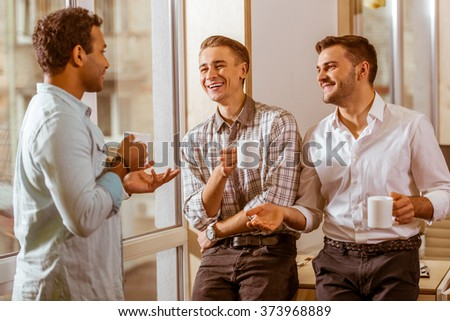 Three young handsome businessmen in casual clothes laughing, talking and drinking coffee while standing in office - stock photo