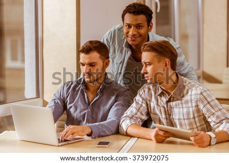 Three young handsome businessmen in casual clothes smiling, discussing ideas, using laptop and tablet while working in office