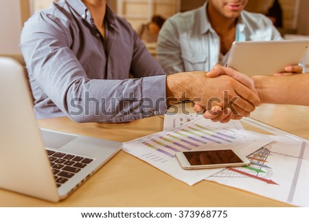 Three young handsome businessmen in casual clothes smiling, using laptop and tablet while working in office. Two men shaking their hands, close-up - stock photo