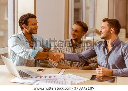 Three young handsome businessmen in casual clothes smiling, using laptop and tablet while working in office. Two men shaking their hands - stock photo