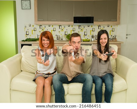 three young happy caucasian people sitting on couch, having fun while playing video game - stock photo