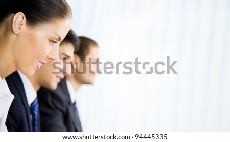 Three young happy successful businesspeople working at office, with copyspace - stock photo