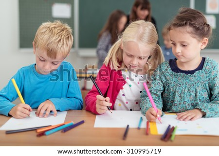 Three young kindergarten pupils having fun drawing with colored pencils on sheets of paper, teacher and student in the background - stock photo