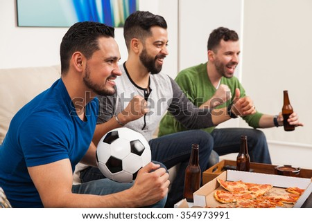 Three young Latin men celebrating a goal while watching a soccer game at home with pizza and beer - stock photo