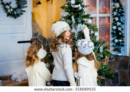three young little caucasian girls standing together near christmas tree holding gifts and smiling sincerely. - stock photo
