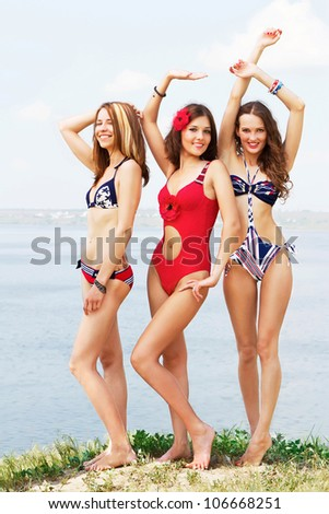 Three young lovely woman having fun on the beach - stock photo