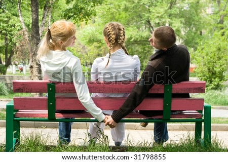 Three young loving people sitting on the bench in park beck at camera