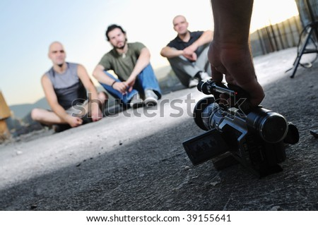 three young man siting on ground while modern video camera recording - stock photo