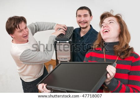 Three young men also hold the new computer. - stock photo