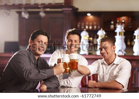 Three young men bob mugs in the bar - stock photo
