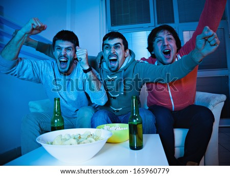 Three young men excited by goal scored during sports competition - stock photo