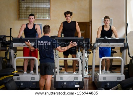 Three young men exercising on treadmills with personal trainer in a gym - stock photo