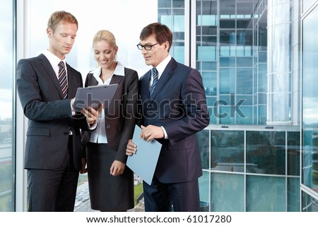 Three young men in business suits in the office - stock photo