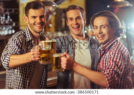 Three young men in casual clothes are smiling, looking at camera and clanging glasses of beer together while standing near bar counter in pub - stock photo