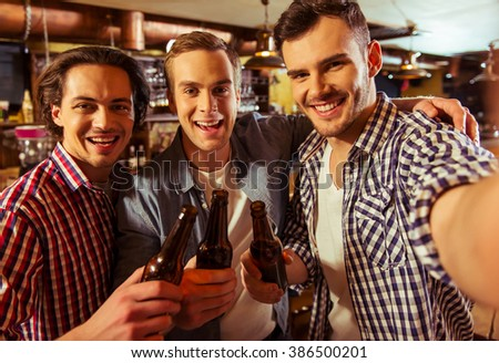 Three young men in casual clothes are smiling, looking at camera and holding bottles of beer while standing near bar counter in pub - stock photo