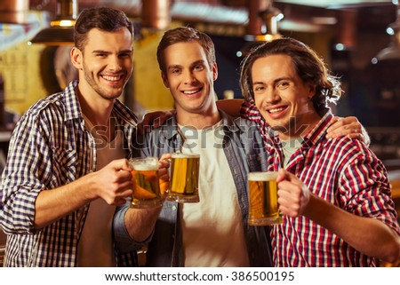 Three young men in casual clothes are smiling, looking at camera and holding glasses of beer while standing near bar counter in pub - stock photo