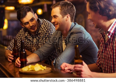 Three young men in casual clothes are talking, eating chips and drinking beer while sitting at bar counter in pub - stock photo