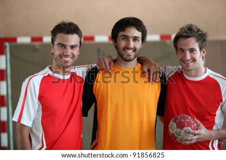 Three young men indoors with hand ball - stock photo