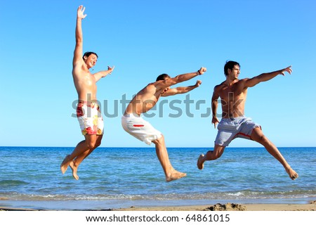 Three Young Men jumping On the Beach - stock photo