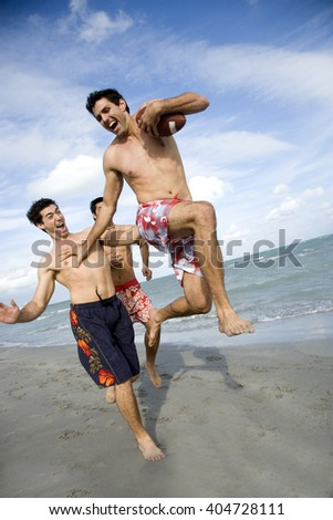 Three young men playing with a ball on a beach - stock photo