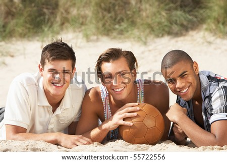 Three Young Men Relaxing On Beach With Football Together - stock photo