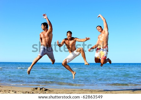 Three Young Men Relaxing On the Beach - stock photo