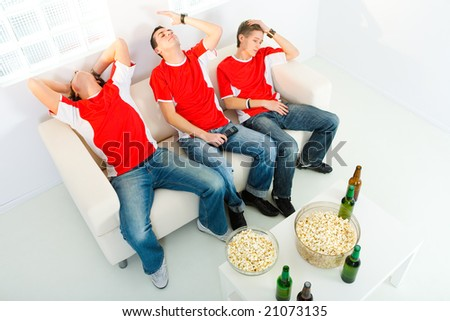 Three young men sitting on chouch and watching TV. They look disappointed. High angle view. - stock photo