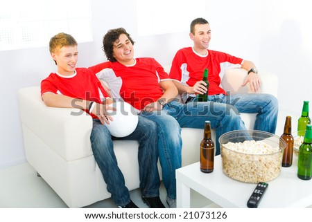 Three young men sitting on couch and watching soccer game on TV. - stock photo