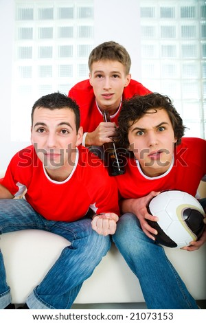Three young men sitting on couch and watching soccer game on TV. Front view. - stock photo
