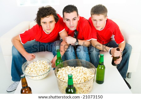 Three young men sitting on couch and watching sport on TV. Front view. - stock photo