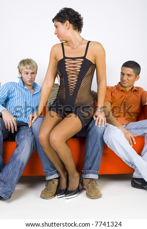 Three young men sitting on orange couch in front of stripteaser. Smiling and looking at her. Front view