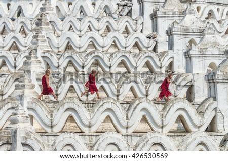 Three young monk are running and jumping on the Mya Thein Tan Pagoda at bagan, mandalay, myanmar - stock photo
