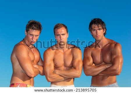 Three young muscular men on the beach