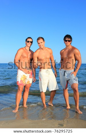 Three Young muscular Men Relaxing On the Beach - stock photo