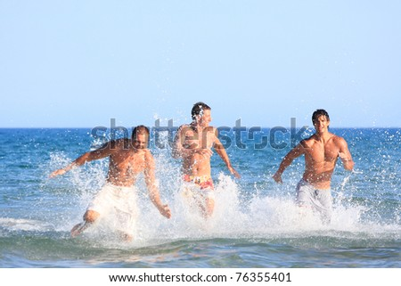 Three Young muscular running in the water - focused on the man on the right side - stock photo