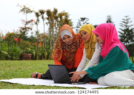 Three young muslim girls with laptop in green park - stock photo