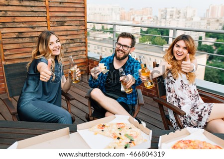 Three young people chilling in chairs on terrace on city background. They have outdoor party, pizza on table, bottles in hand. They stretch hands to the camera and smile.