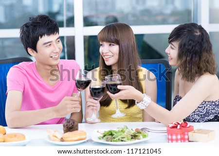 Three young people clinking glasses at party table - stock photo