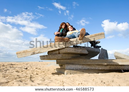 Three young people enjoying a beautiful autumn afternoon on the beach, sitting on a pile of concrete slabs - stock photo
