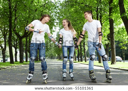 Three young people go for a drive on rollers - stock photo