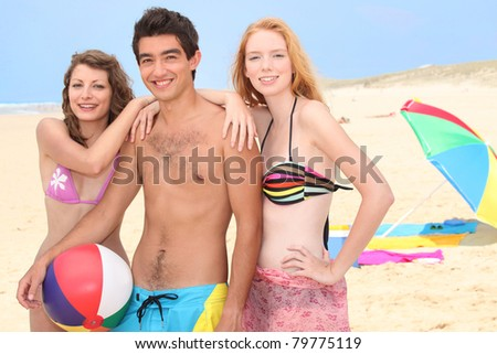 Three young people hanging out on the beach - stock photo