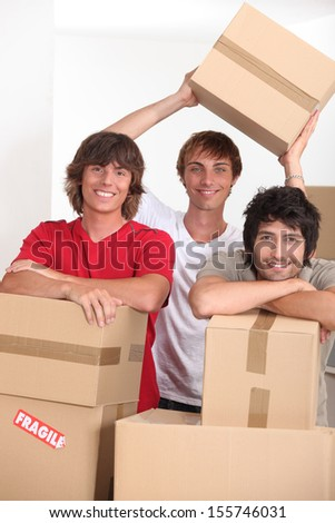 three young people in a room full of cardboard boxes