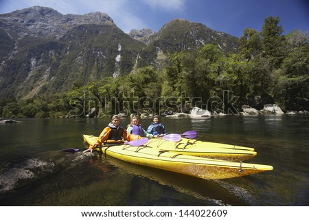 Three young people kayaking in the lake with mountains in background - stock photo
