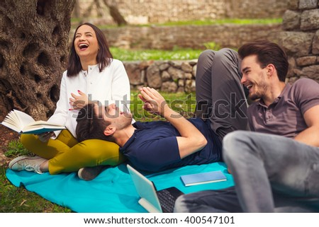 Three young people on picnic sitting on blanket under the olive trees - stock photo